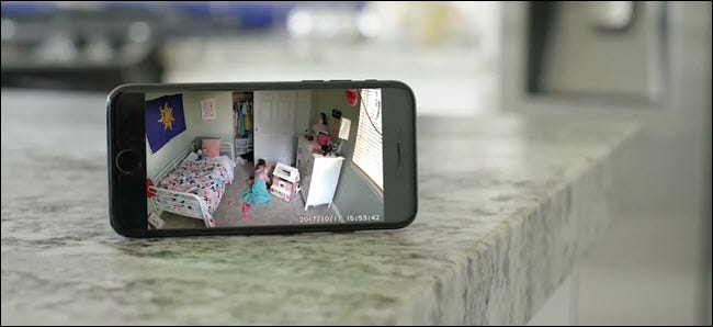 An iPhone showing a Wyze Cam feed of a child playing in her bedroom.